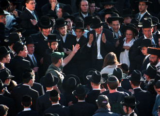 An Israeli Border Policeman waves a large crowd of ultra-orthodox Jews away as they taunt a conserva..
