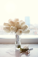 Bridal bouquet, wedding rings and boutonniere of tender white roses on the windowsill against the backdrop of the city