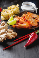 Asia culture. Fresh raw shrimp, noodles, chili pepper, ginger, soy sauce in a bowl on a wooden table. Eating seafood. Dark background.