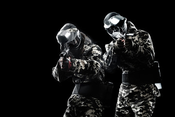 Heavily armed masked paintball soldier isolated on black background. Ad concept.