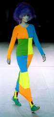 A model for Comme des Garcons parades on stage with a large geometric multi-coloured ankle-length sk..