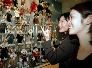 Japanese college students Mariko Tomura (L) and Sayaka Ouchi giggle as they look at dolls of cartoon..