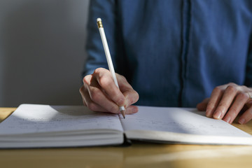 hand of a woman writing in a notebook with a pencil