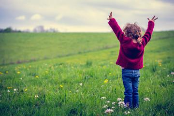 une fillette levant les bras devant un grand pré