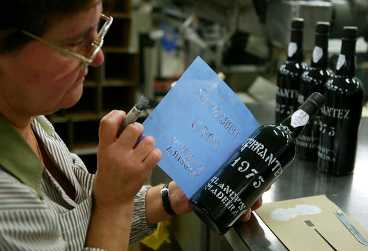 -PHOTO TAKEN 13OCT04- A worker stencils a bottle of vintage Madeira wine by hand at the Madeira Wine..