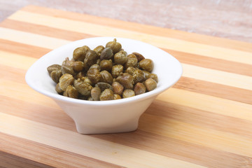 bowl with fresh capers on wooden table