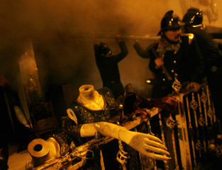 Firemen tend to a fire at multistorey clothing shop as salvaged mannequins lie outside in Mumbai