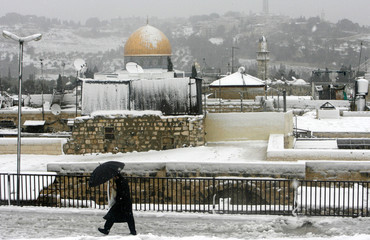 A Jewish man walks on a roof top with the Dome of the Rock Mosque in the background during a snow storm in Jerusalem
