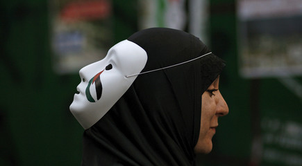 A muslim woman wears a mask on the back of her head during a protest against the air strikes on Gaza outside the Israeli Embassy in Buenos Aires