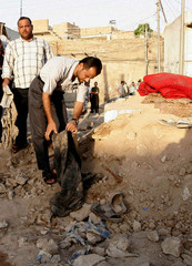 Residents inspect ruins of popular coffee shop after suicide bomb attack in the town of Tuz Khurmatu north of Baghdad