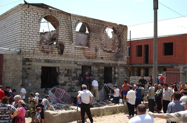 PEOPLE LOOK AT A PARTLY DESTROYED PRIVATE HOUSE IN THE OUTSKIRTS OF MAKHACHKALA.