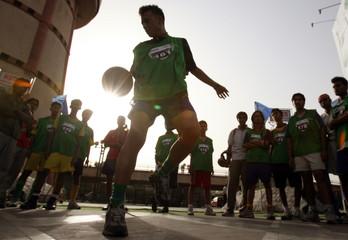 A young soccer player displays his skills during a street soccer show in New Delhi