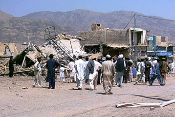 Pakistani tribesmen gathered in front of demolished shops in the main bazaar of Wana.
