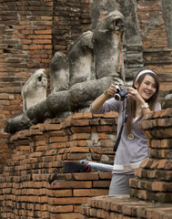 Girl takes picture next to decapitated heads of Buddha figures at Wat Chai Wattanaram in Ayutthaya