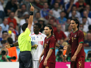 Referee shows France's Louis Saha a yellow card during their World Cup 2006 semi-final soccer match against Portugal in Munich