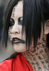 A girl  with Japanese kanji characters written on her face hangs out in Tokyo's Harajuku district