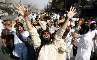 Men protest the death of Muslim cleric Sarfraz Naeemi through the streets of Lahore, hours after he was killed by a suicide bomber at his mosque compound