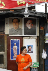 Yu stands in her dried fruit and nuts kiosk adorned with posters of late Chinese leaders Deng and Mao plus the current Premier Wen in Beijing