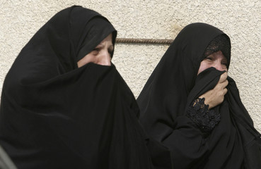 Women cry while waiting to claim the body of a policeman relative who was killed in an ambush, in Basra