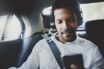 Young smiling african man using smartphone while sitting on backseat in taxi car.Concept of business people traveling.Blurred background.