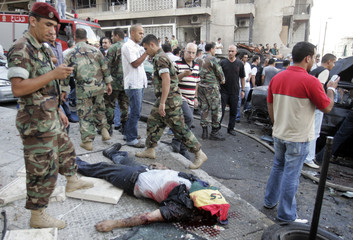 A Lebanese soldier stands next to a body after an an explosion in eastern Beirut