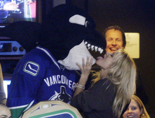 Actress Anderson licks Vancouver Canucks mascot Fin during a break in the NHL game between the New York Rangers and the Canucks in Vancouver