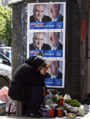 A woman sells groceries in front of Serbian Radical Party's electoral posters in the northern Kosovo town of Mitrovica