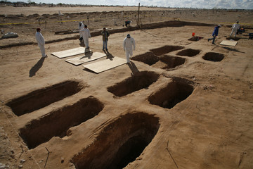 Forensic workers work at a mass grave at a cemetery on the outskirts of the border city of Ciudad Juarez
