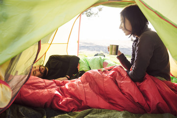Couple traveling, spending time in tent, drinking coffee in the morning