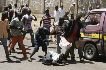 A woman is robbed as she returns with goods in the Kibera slum after post-election riots in Nairobi