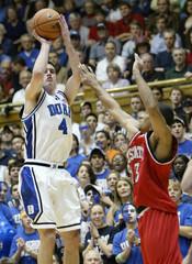 Duke University's Redick shoots over the defense of North Carolina State University's Bennerman in Durham