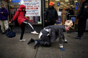 Passer-by kicks performance artist Mark McGowan as he crawls on the street dressed in a President George W. Bush mask in New York
