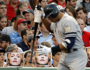 Fans hold up pictures of Madonna behind the New York Yankees' Alex Rodriguez as he stands in the on deck circle in the third inning of the Yankees MLB baseball game against the Boston Red Sox at Fenway Park in Boston