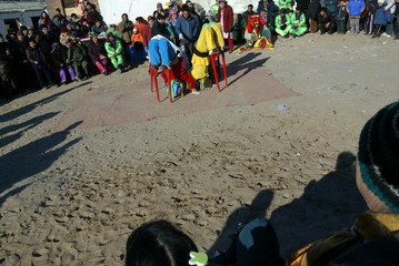ACROBATS ON STILTS BEND BACKWARD TO PICK UP CIGARETTES AT A TEMPLE FAIR IN BEIJING.