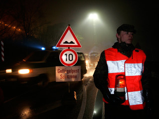 German soldier stands beside disinfection barrier for cars and pedestrians on island of Ruegen