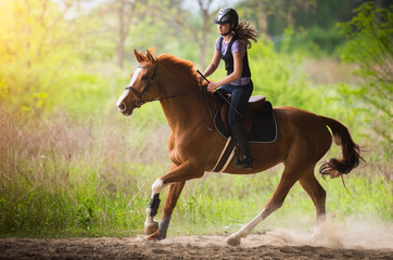 Young pretty girl riding a horse with backlit leaves behind in spring time