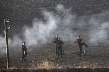 North Korean border guards throw stones towards the photographer as they work on a field at the Yalu River near the North Korean city of Hyesan