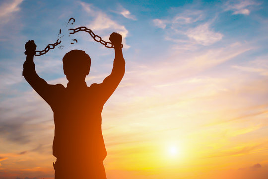 Silhouette image of a businessman with broken chains in sunset