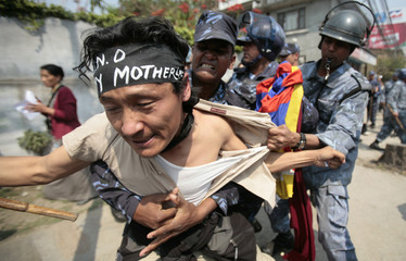 A Tibetan protester struggles with police officers in front of the UN building in Kathmandu