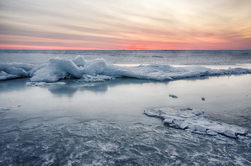 Abstract frozen winter sunrise seascape with ice and colored the sky.