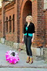 Pretty blonde girl walking with comic pug. Funny dog with tongue hanging out near brick wall on the sidewalk