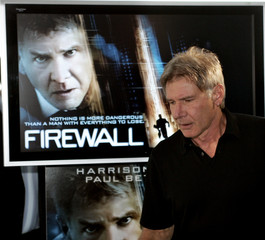 Harrison Ford passes a promotional screen as he arrives at a news conference in Sydney