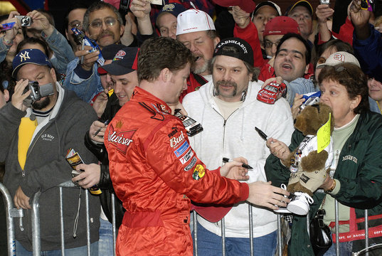 Earnhardt Jr. sign autographs after the top ten NASCAR drivers celebrated the end of their season with a lap through Times Square in New York