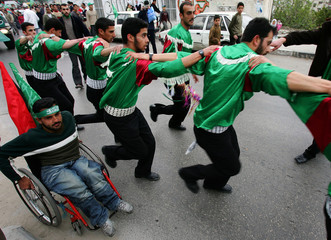 Palestinian members of the Hamas movement dance on a street during a rally in the West Bank city of ...