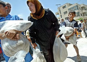PALESTINIANS CARRY BAGS OF FOOD DISTRIBUTED FROM THE UNITED NATIONSRELIEF AND WORKS AGENCY FOR ...