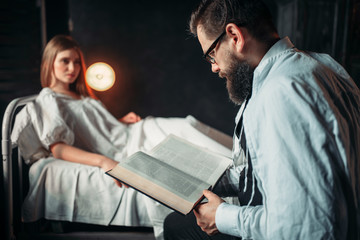 Man reading book against ill woman in hospital bed