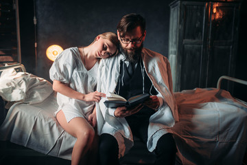 Love couple reading a book in hospital room