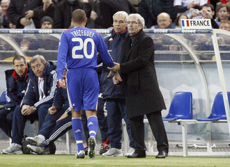 France's Trezeguet is greeted by coach Domenech as he leaves the field during a friendly soccer game against Britain at the Stade de France in Saint-Denis, near Paris