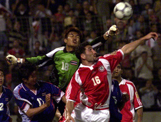 THAILAND'S GOALKEEPER WANGCHAN CLEARS THE BALL FROM LEBANON'S KASSAS IN BEIRUT.