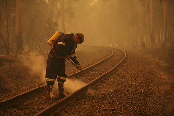 A firefighter douses burning railway sleepers as bushfires sweep across the countryside near Cape Town